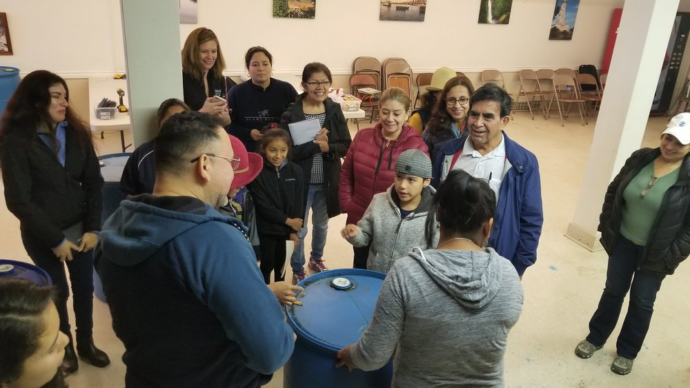 Latino community members in Monroe learn how to build a rain barrel to collect rainfall on their properties for use in watering gardening beds.