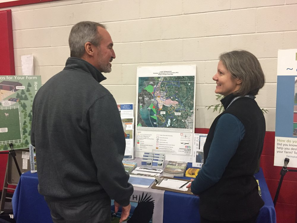 Kathryn talking to a booth participant about the Stillaguamish PIC