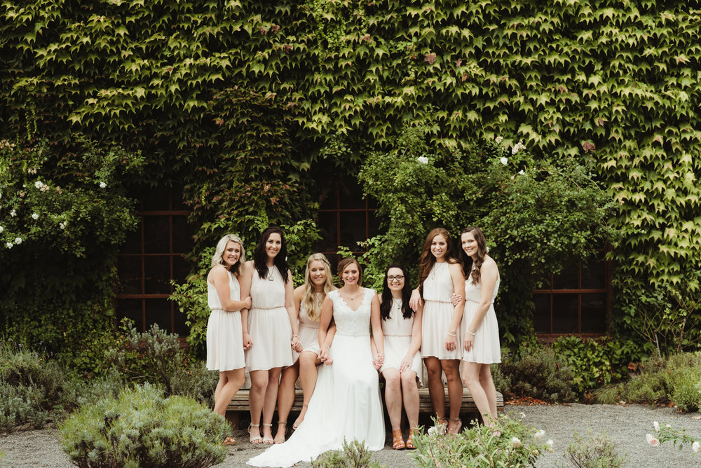 Bridal party portrait in front of ivy wall.