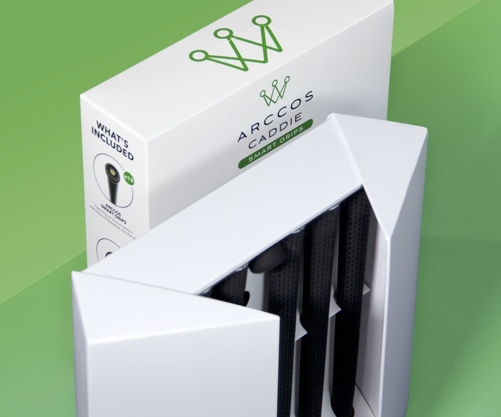 Arccos Caddie - October 2018   For the Arccos Grips product, Caddie, we created a new format of physical packaging. Each package opens to reveal two layers of sensor embedded grips, along with a guide booklet and putter sensor.  Care was taken to create a strong physical connection with the prior sensor pack, through materials, opening features and the slide on printed sleeve. This helps create a strong brand dna and allows the messaging to concentrate more on communicating the product features and benefits.