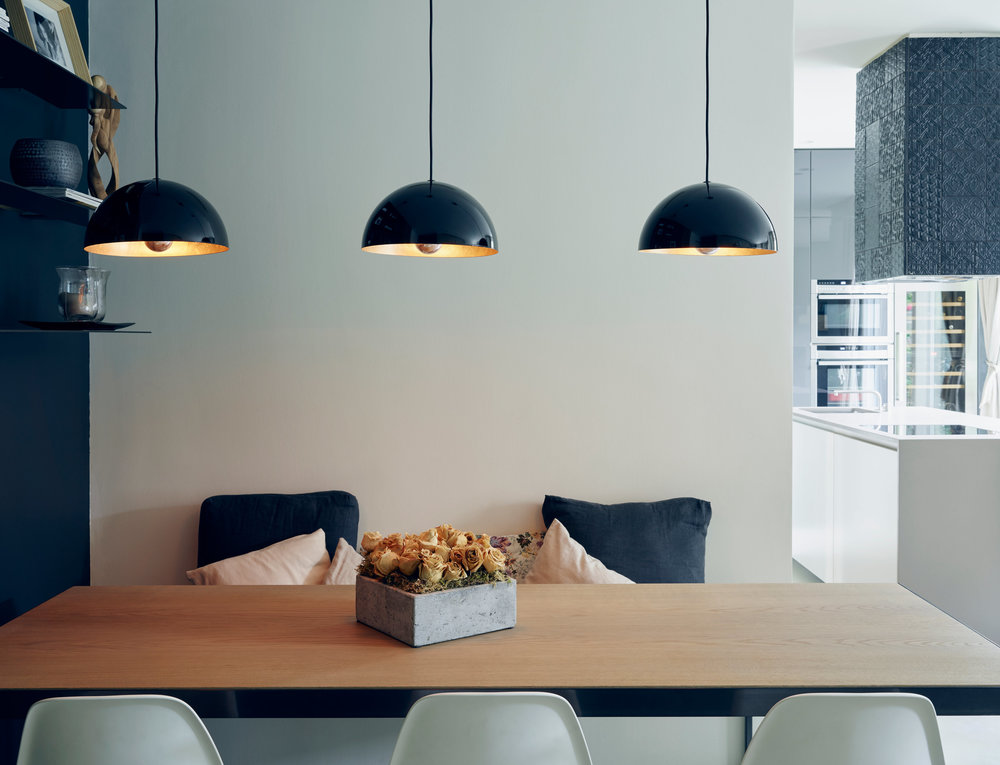 Photo by Nick Ballon.Three simple light fixtures with a pretty brass finish add a warm glow to a cool-toned room.