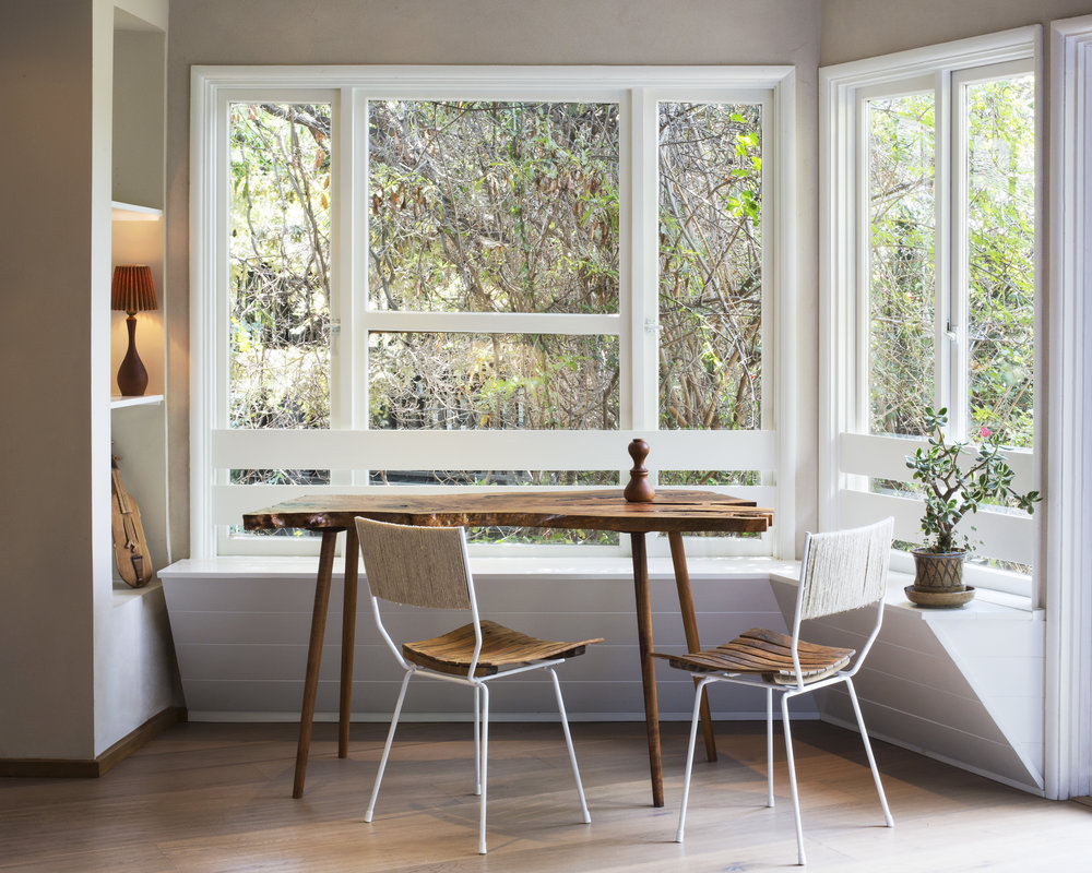Photo by Charlie Richmond Coffing. A beautifully simple shiplap built-in banquette balances perfectly with a live edge table, making the most of the abundant natural light.
