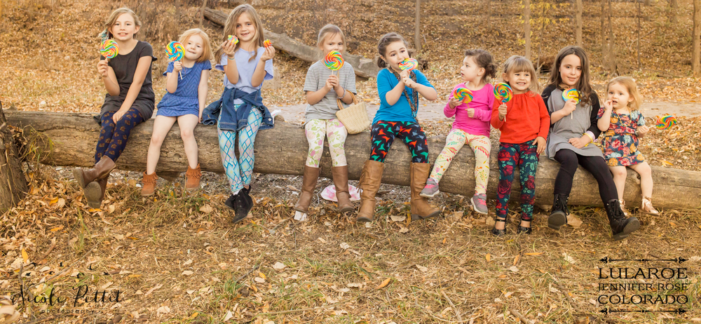 A bunch of little girls eating lollipops on a fallen tree modeling Lularoe with Jennifer from Colorado at the Poudre River Trail in Fort Collins, Colorado