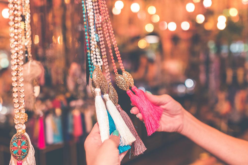 Women choosing bijouterie in the store. Bali island. Woman hands.