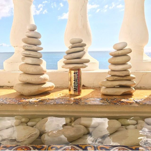 """Happy Fri-YAY!🍻 This is my version of a #PuertoRican zen rock stack 😜 Got into #puertorico 🏝last night after a long day of travel; happy to be """"home"""" here for a few days while @catchingcamp works to set up free camps for baseball/softball catchers here through his new non-profit! ⚾️ So if any of my friends in Puerto Rico have contacts with baseball players or organizations, DM me! 💌  Also haven't booked a place to stay yet from today- next Wednesday so if anyone knows of a great #airbnb or hotel that I should check out that we haven't been to before, let me know! 💕 I will be putting together a blog post after this trip to let you all know where to go and what to do since this is my FAVE place to jet to! 🏝 🇵🇷 Signed a contract this past week for WKNDR design for a big interior design project that will really kick up in November but LOTS of pre-planning to do now... in paradise for a few days. 🙌  Snapped this photo while staying at @hdprinconpr 📸 . . . . . . . . #interior #design #beer #beerstagram #medalla #beers #baseball #softball #catchers #whateverpuertorico #zen #rockstacking #ocean #realestate #vacation #getaway #adventure #explore #luxury #hotel #travel #interiordesign #designer #island #islandlife #luxurylifestyle #puertoricobaseball"""