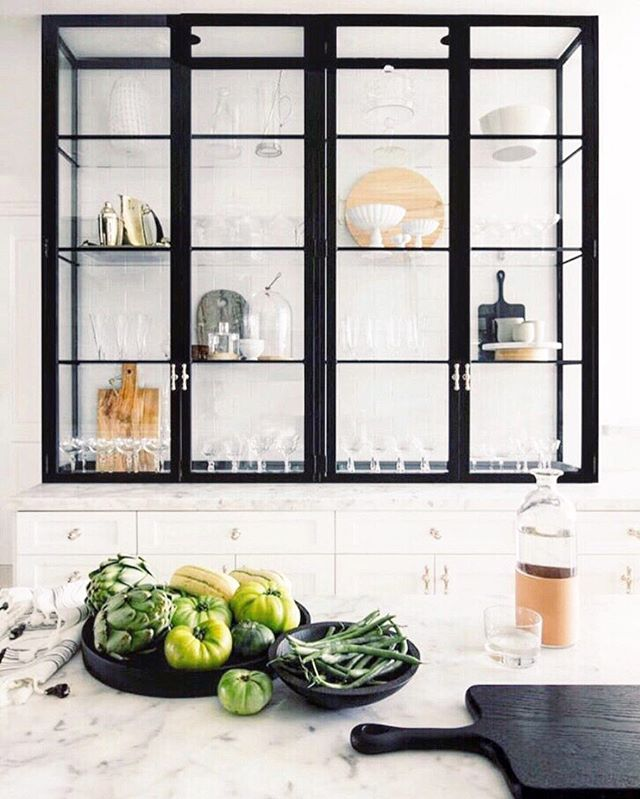 Please, someone out there who is in the midst of redesigning their kitchen, add 👏these👏glass👏cabinets👏 A few years ago, exposed shelving was all the kitchen rage and I was here for it, but I am so amped for this glass window pane trend. With the black metal frame, it's so elegant and sophisticated. Add in some spot lighting up top and boom- immediate evening ambiance. ✨The kitchen is an area I don't like clutter out with decor but the fact that you could throw a few cool cutting boards or barware vignettes in like this gives makes me😍😍😍😍 📸: @smpliving  #interior #interiordesign #interiordesigner #kitchen #renovate #renovation #modern #farmhouse #kitchengoals #style #nyc #hamptons #boston #organic #farmhousestyle #farmersmarket #kitchendesign #bar #finditstyleit #designlife #architecture #realestate #realestateagent #builder #custom #housetour #styleinspiration #cabinets #homestyle #modernhome