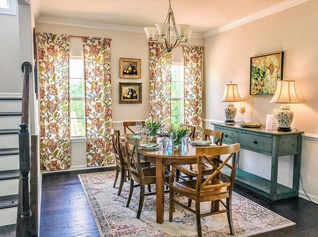 """When design clients come into a new house with some of their own belongings, the fun is figuring out where to put them all and what has to be added to tie the space together. 🤔 With the Morris family's new custom @ryanhomes  house in Charlottesville, VA I opted for some really fun curtains from @wayfair to make the colors pop from their beautiful artwork over the buffet by @mollywrightart 🖼 and their #antique ginger jar lamps. Also LOVE the heirloom still life paintings between the windows! 💗 👉Fun Fact: the curtains were about $280/pair so we just got 1 pair and had a local seamstress cut and sew them into 4 panels for only $40 more! 👏👏 #DIY win!🕺💃🔥 Rug by @rugs_usa 💗 Head to my insta story for the """"Before"""" shot! . . #interior #interiordesign #interiordesigner #art #boston #custom #realestateagent #renovation #homedesign #designer #realestate #mydomaine #dwellmagazine #hgtv #fixerupper #diningroom #wayfair #nyc #charlottesville #virginia #richmond #cville #farmhousestyle #farmhouse #finditstyleit #interior123 #traditionalhome #customhome"""