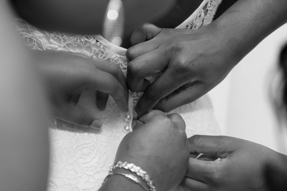 bridesmaid helping bride get dressed black and white