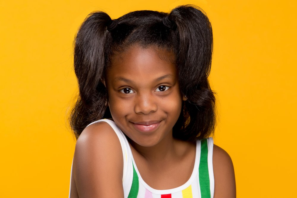 girl with pigtails against yellow background in a striped top