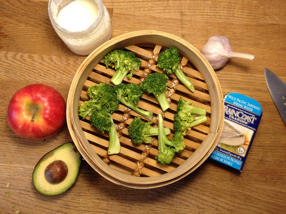 Top left to bottom left, clockwise: milk kefir, garlic, sardines, lightly steamed broccoli, avocado, fuji apple