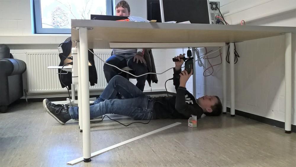 Jan installiert Kabelkanäle unter den Tischen.