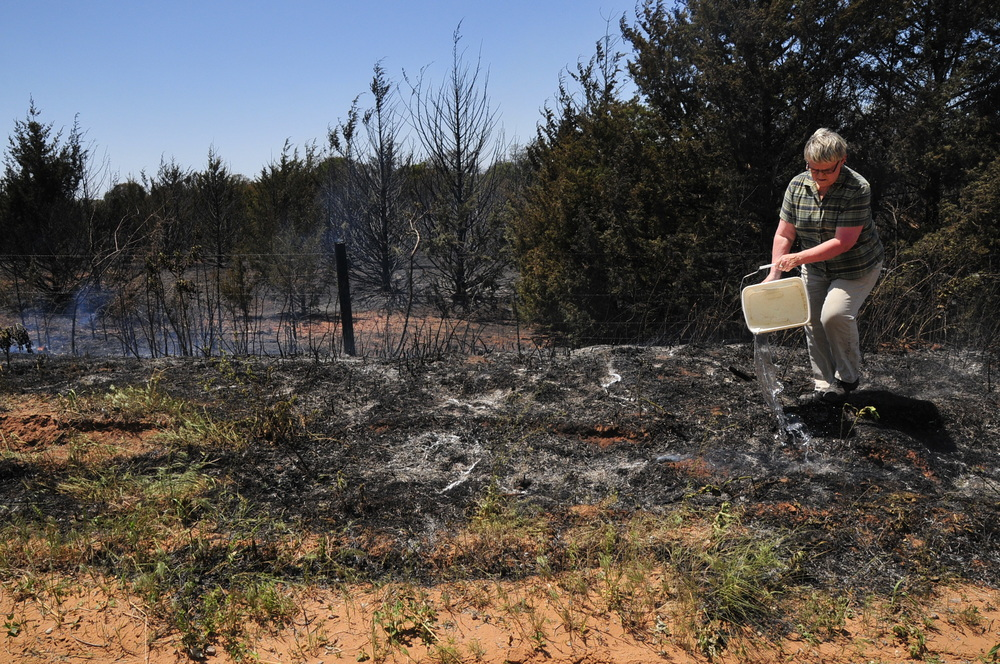 Wilma Rogers pours water on a hot spot across the road from his home in hopes of keeping the fire from spreading on Monday, May 5, 2014, in Guthrie, Okla. (AP Photo/Nick Oxford)