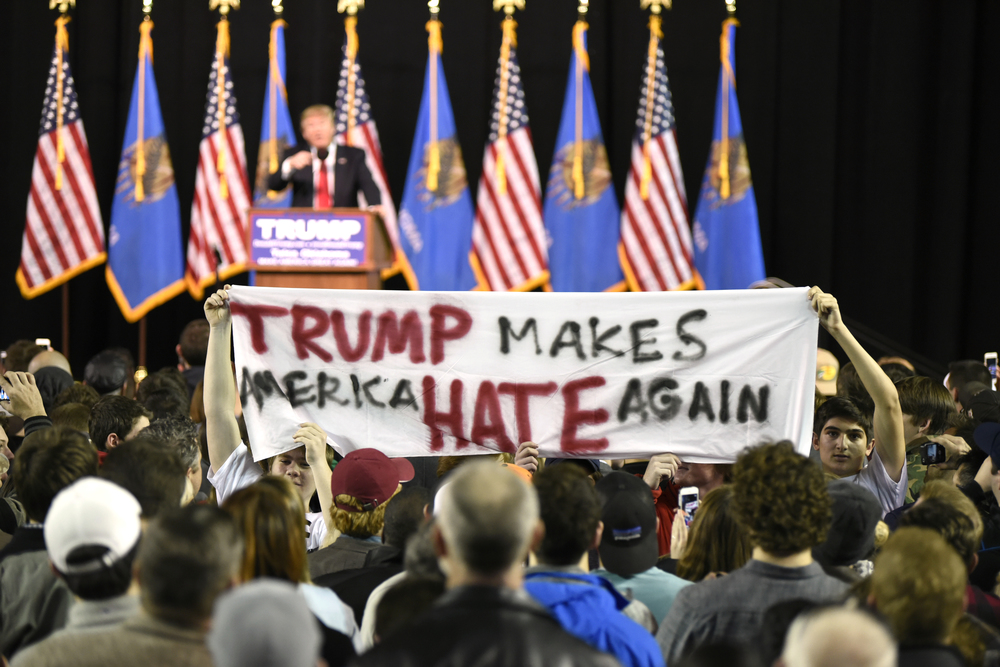 Protestors hold up a sign towards the crowd at a rally for U.S. Republican presidential candidate Donald Trump at Oral Roberts University in Tulsa, Oklahoma, January 20, 2016. REUTERS/Nick Oxford