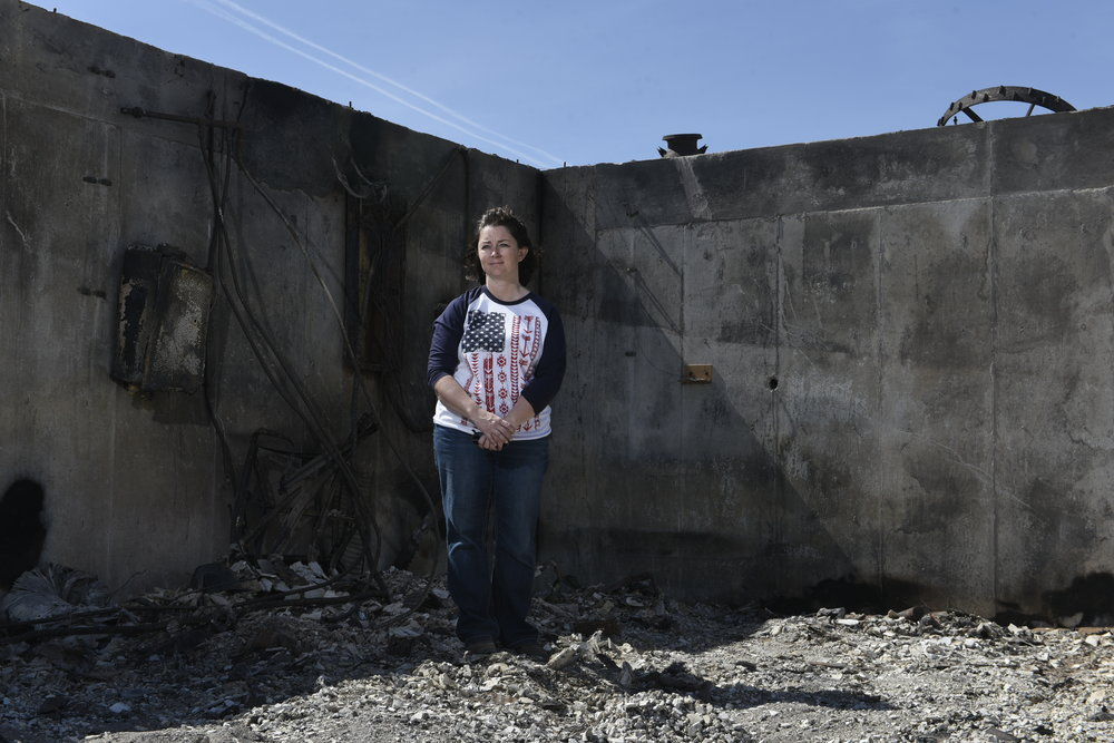 Jenny Betschart stands in the ashes of what was once her family's home outside of Ashland, Kansas. The Betschart family lost their house and countless acres of ranch land after wildfires swept through parts of Kansas, Texas and Oklahoma last week.  Nick Oxford for The New York Times