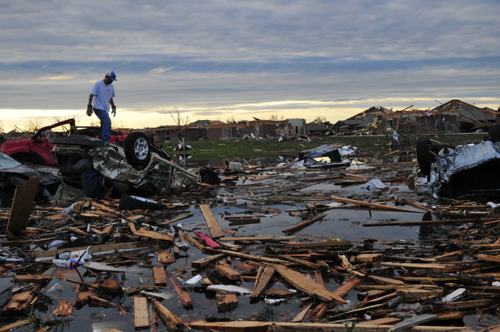 Mark Heflin searches for some belongings in a pond full of debris and cars in a neighborhood that took a direct hit from yesterdays tornado on May, 21 in Moore Oklahoma