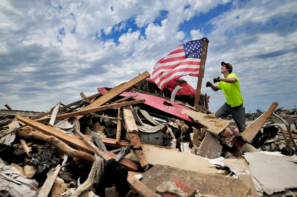 Franklin Van Beckum, a volunteer from Edmond, hangs a flag that he found amid the destruction on Thursday, May 23 in Moore OK.PHOTO SENT ON SPEC