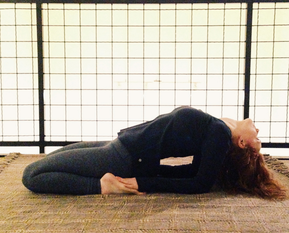 Leah in a variation Hero Pose stimulating proper function of the thyroid and digestive system, stretching the abdomen, hip flexors, knees, ankles and feet. Easy modifications make this posture available during class for all to benefit.