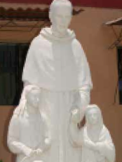 A statue of Father Edward Chapman, O.S.A., with two children stands outside the Augustinian friary in Morropón, Peru.