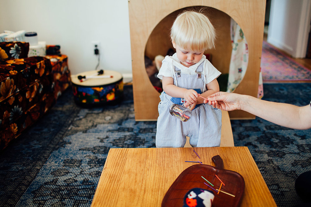 Toddler playing with colored sticks at home