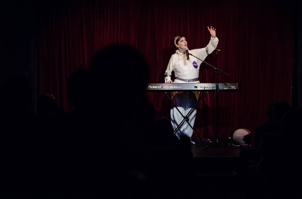 Me and the back of an audience member's head during To The Moon & Back at MICF.   Photo by Brett Scapin Photography