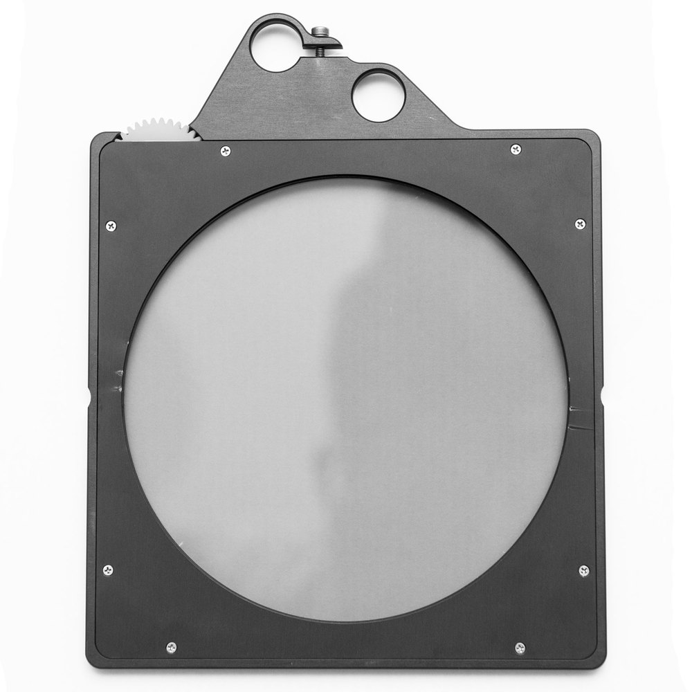Image of Cinefade's Filter Tray, an aluminum housing holding a round polarizing filter with a geared wheel on the top left corner and small holes on top that act as a motot mounting point and handle.