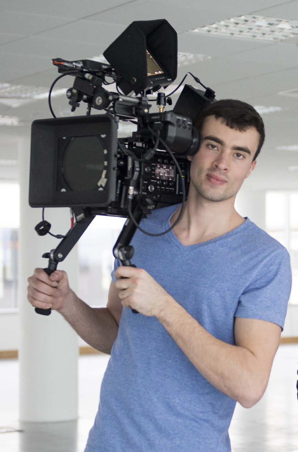 Image of Oliver Janesh Christiansen, the Founder of Cinefade and an incredibly handsome young man holding a camera on his shoulders.