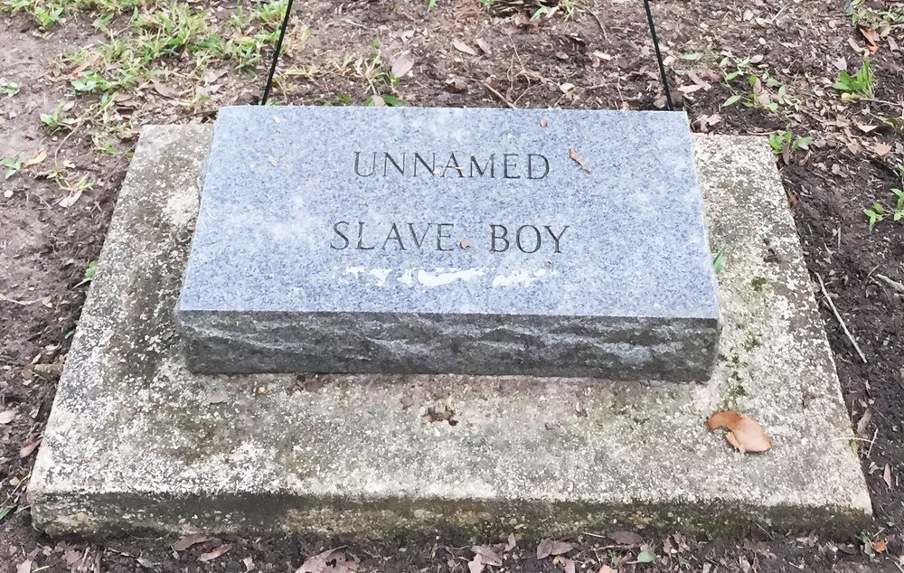 "The headstone for gaston currently reads: ""unnamed slave boy"""