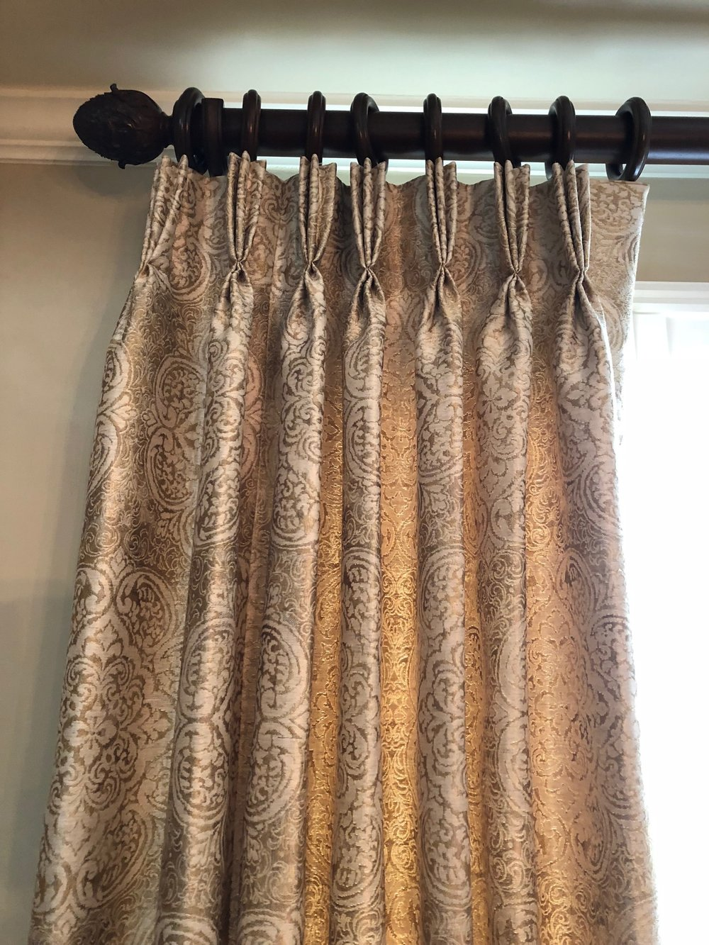 Custom draperies with reach gold and black fabric.
