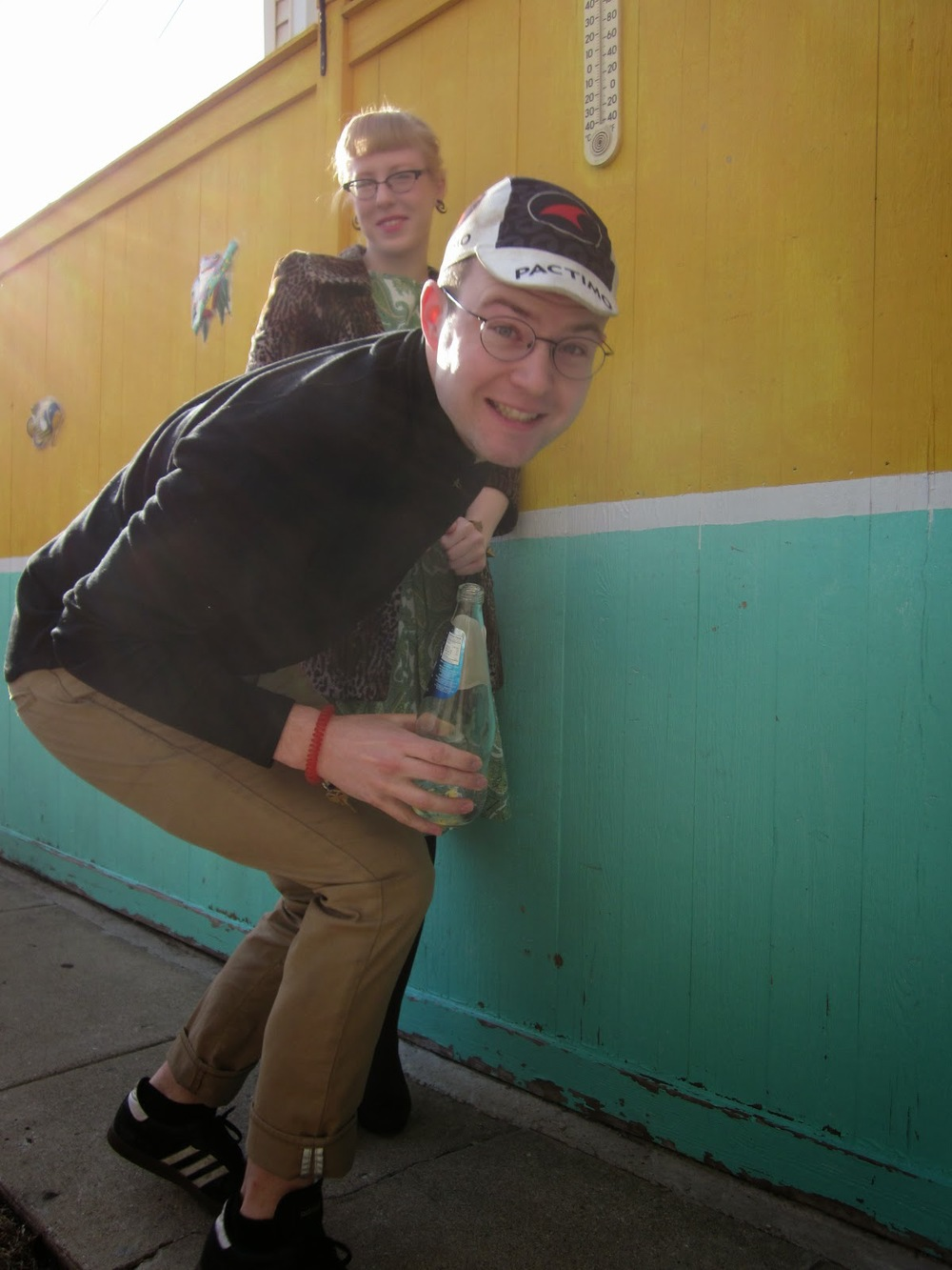 a woman leans against a fence in the background, while in the foreground a young man makes a funny face into the camera
