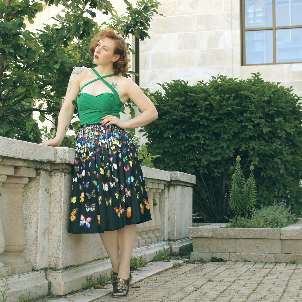 Zella Maybe in a butterfly print skirt with a green top and gold shoes. At the Shedd Aquarium looking out over Chicago. Vintage fashion blogger.
