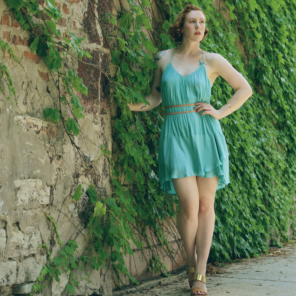 Woman with red hair with 1950s style waves in a drapey blue chiffon dress and gold sandals, standing in front of a brick and ivy wall in Chicago. Chicago vintage blogger.