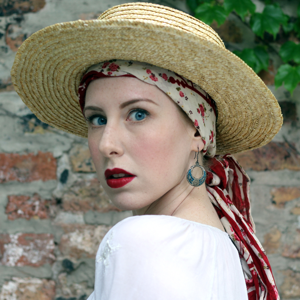 Zella Maybe in a red floral headscarf and straw hat, with red lipstick, turquoise earrings, and a white blouse.