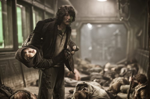 Kang-Ho Song carries Ah-sung Ko in Snowpiercer. A person instead of a pack, genius. Photo Credit: Snowpiercer (2014).