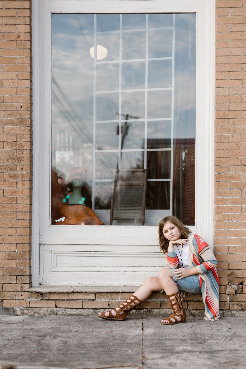 The reflection of the sky and utility pole in the side window of the DA Varnado museum adds to the drama of this tween portrait captured by Chris Ginn Photography during one of his Franklinton tween portrait sessions.