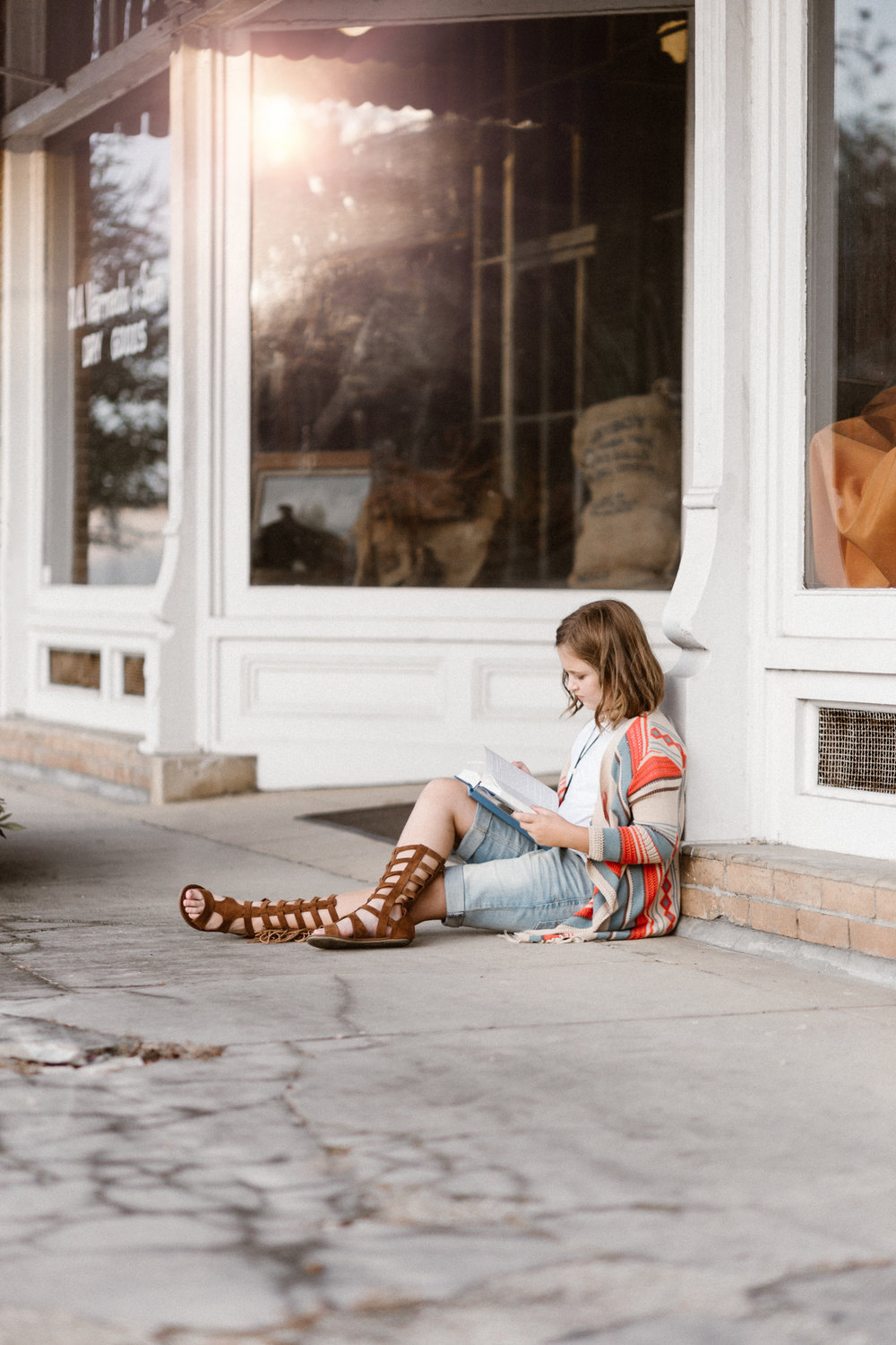 The sunset captured in the window of the DA Varnado Museum in Franklinton, Louisiana enhances the magic of reading during a recent Franklinton, Louisiana tween photo session by Chris Ginn Photography.