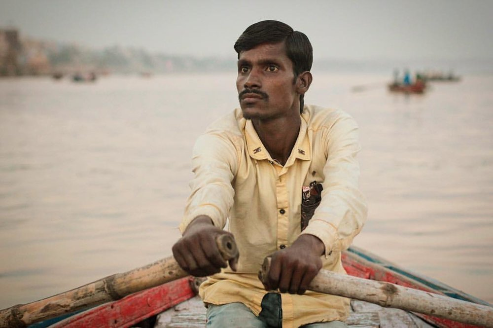 The face of a man determined to not smell the pile of burning bodies. — in  Varanasi, India .