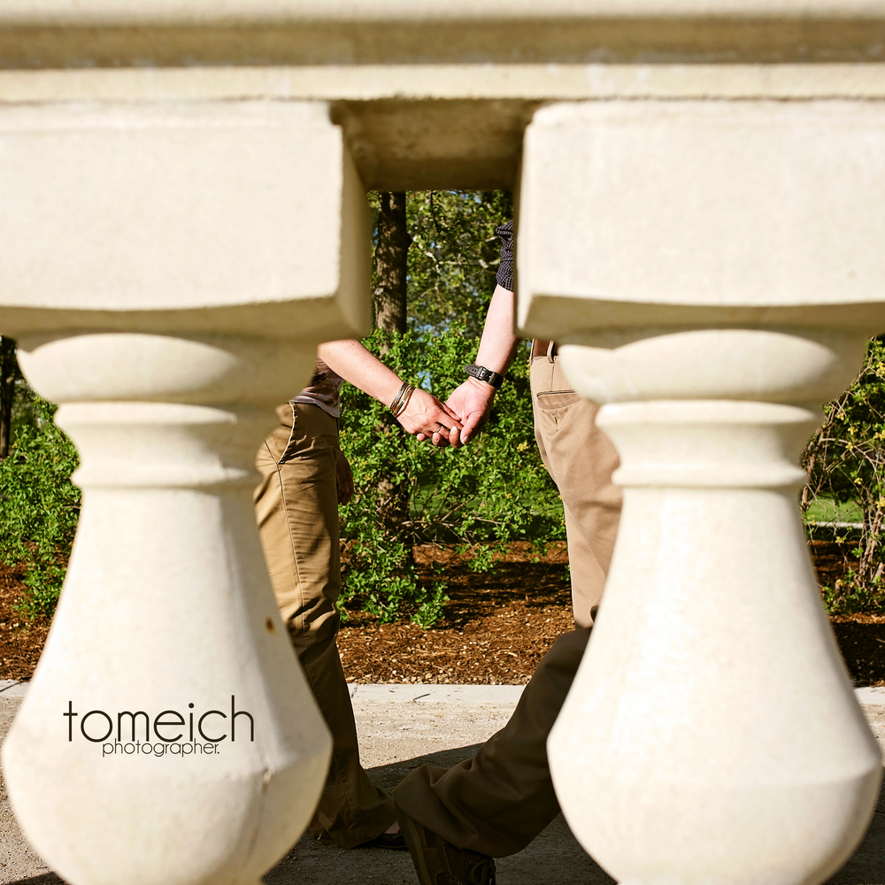 couple holding hands framed by decorative concrete at art hill forest park.  #lovestl #arthill #forestparkengagement