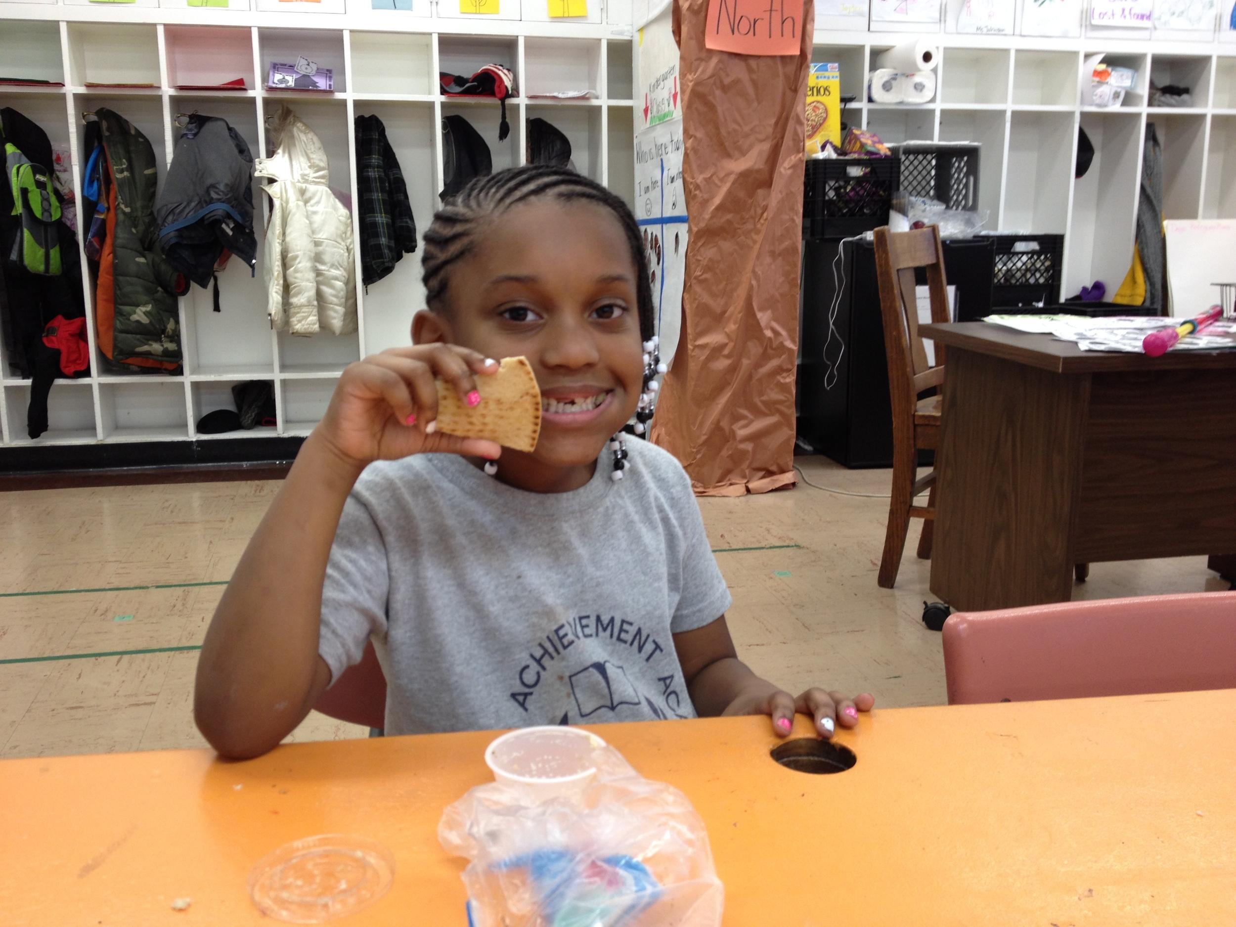 Janiya has pita & hummus for snack.