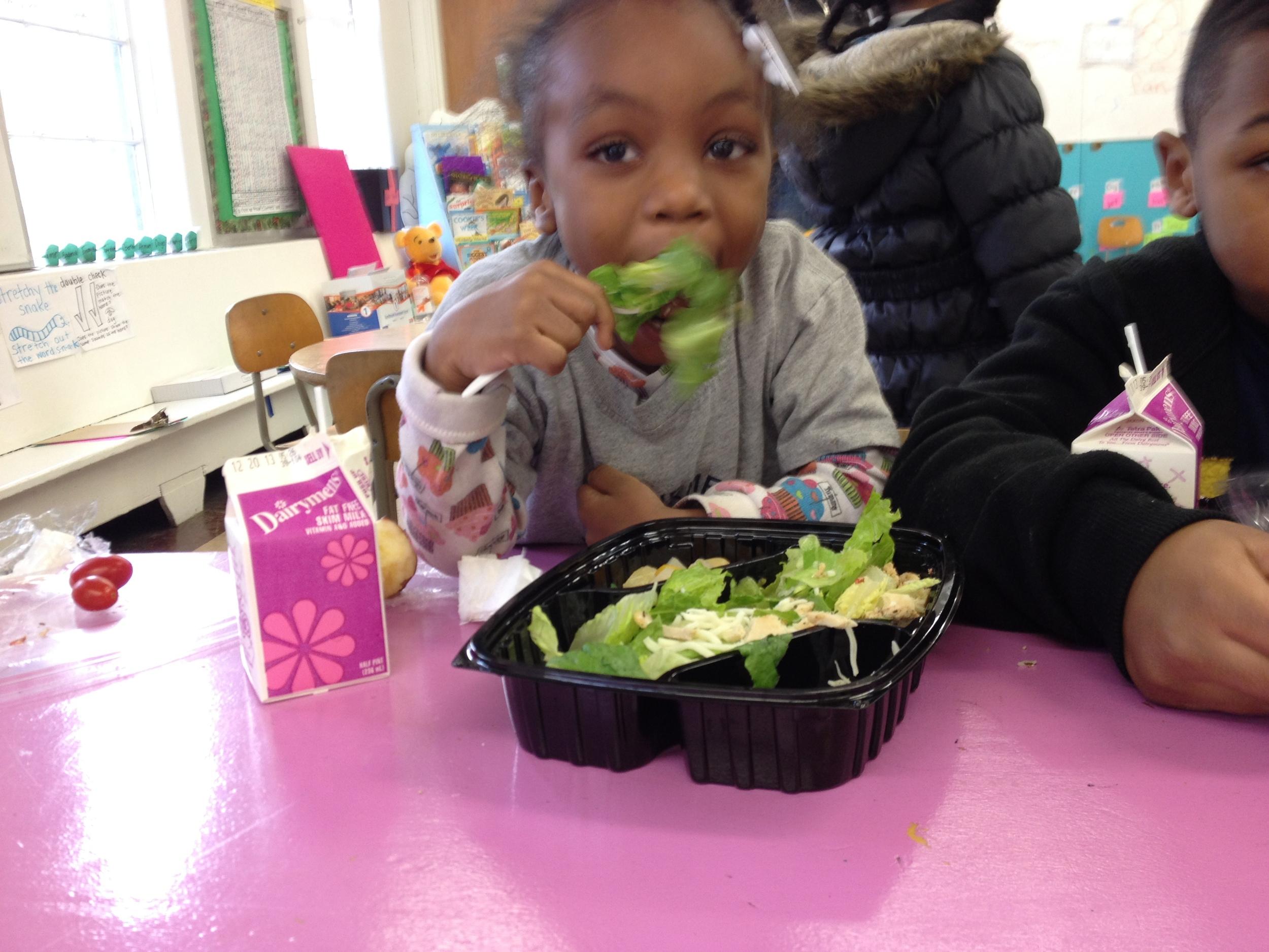 Kindergartener Brooke chomps on a Caesar salad for lunch.