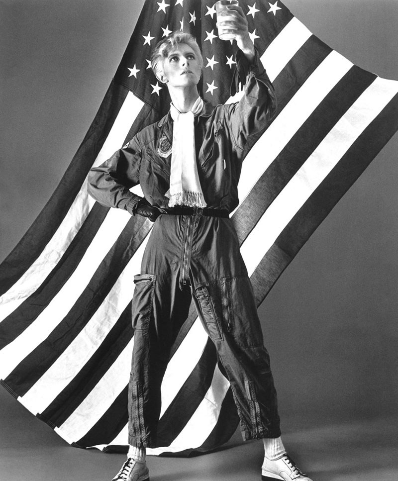 David Bowie David Bowie poses in front of US flag for a portrait by Michael Ochs, 1976