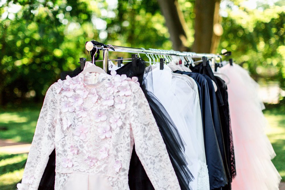 The runway looks hanging on the garment rack before the garden party fashion show.