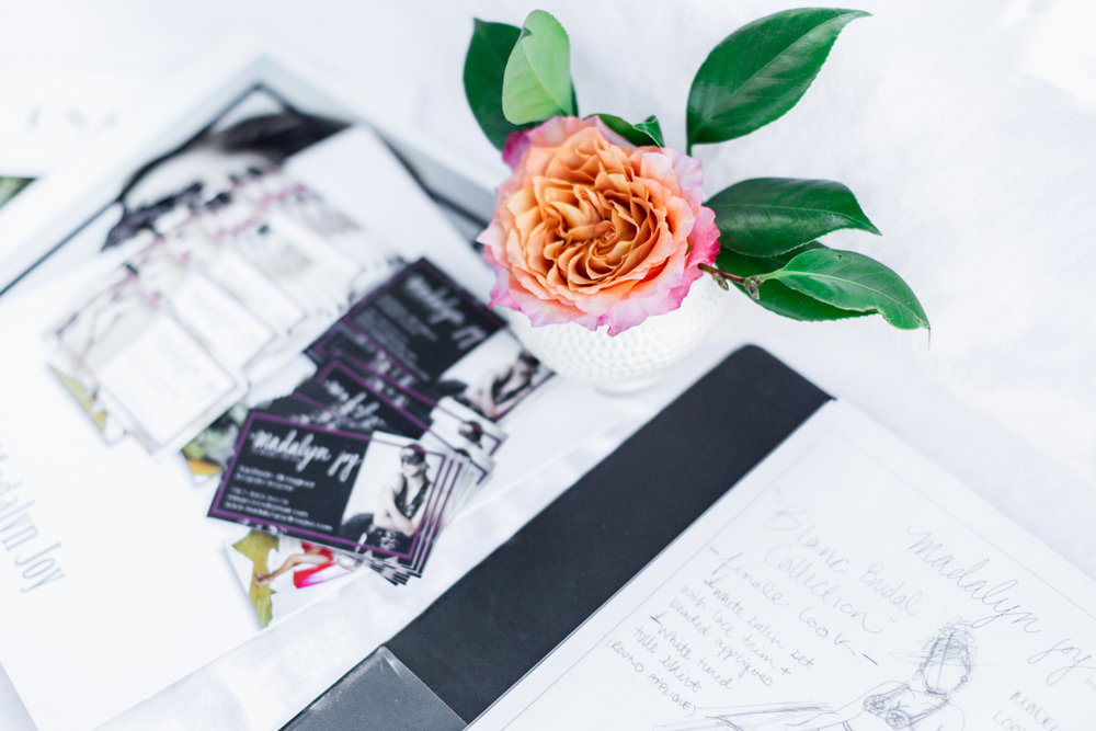 Madalyn Joy Designs business cards and sketches amidst a perfectly placed La Tulipe centerpiece.