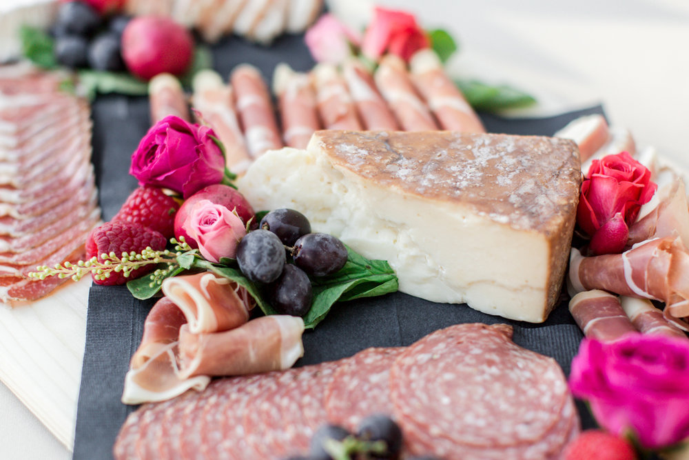 A delicious charcuterie board adorned with decadent cheeses and savory meats.
