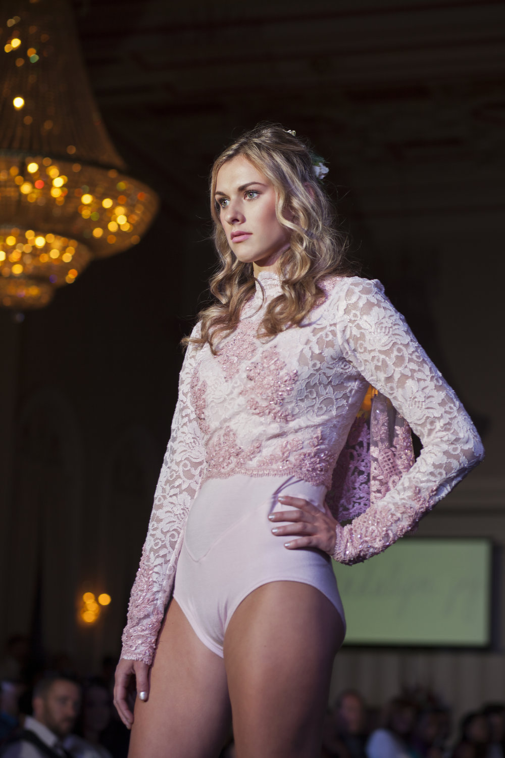 Holland Huron strikes a fierce pose on the runway wearing a blush pink leotard and embellished crop top with a capelet.