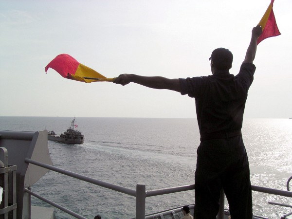 Signalman Seaman Adrian Delaney practices his semaphore aboard the amphibious dock landing ship USS Harpers Ferry (LSD 49) during an at-sea training evolution with the Royal Thai Navy tank landing ship Her Thai Majesty's Ship (HTMS) Prathong (LST 715) during the Thailand phase of exercise Cooperation Afloat Readiness and Training (CARAT). (U.S. Navy photo by Journalist 3rd Class Alicia T. Boatwright)