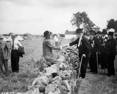 "1935: At the 75th anniversary of the Battle of Gettysburg, Confederate and Union veterans shake hands across the stone wall at ""the Bloody Angle,"" widely regarded as the ""high water mark"" of the Confederacy."