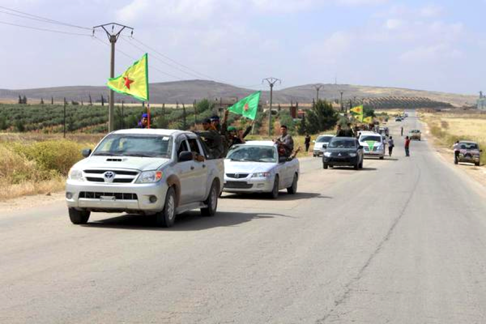 Photo by Jack Shahine, depicts YPG vehicles and infantry on the move.