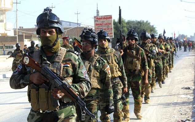 Iraqi security forces march on the outskirts of Najaf (Reuters)