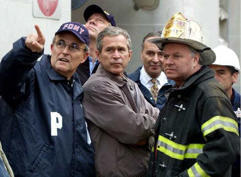President George W. Bush, Rudy Giuliani, left, and New York Governor George Pataki, second from left, Sen. Charles Schumer, D-N.Y., second from right, and New York City Fire Commissioner Thomas Van Essen, right, look toward the fallen buildings during a tour of the World Trade Center, Friday, Sept. 14, 2001 in New York. (Doug Mills, AP)