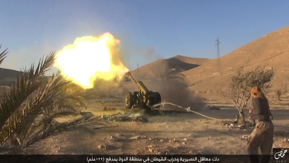 """Pounding  Nusayri  and  Hizb Al Shaytan  (party of Satan) bunkers in the  Ad Dawwah  region with a 122 mm cannon."" Bottom right: Wilayah Homs Media Office logo."